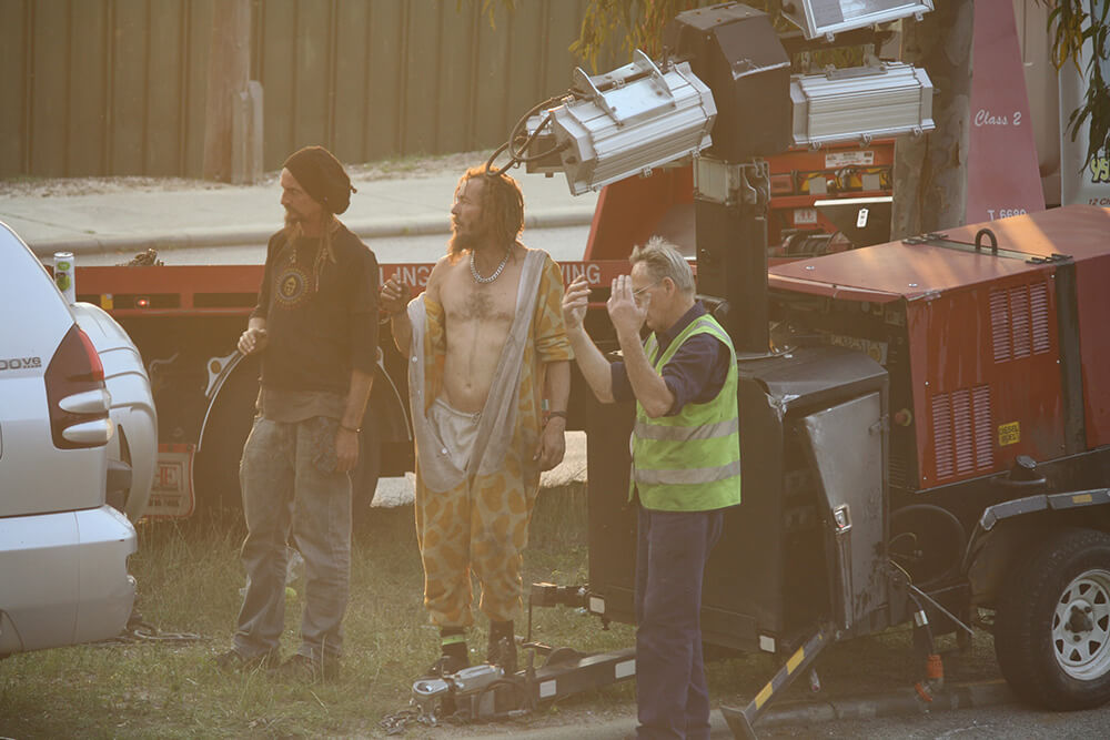 A man in a giraffe onesie and others attempt to reattach the trailer to the vehicle. Photograph – Robyn Molloy.