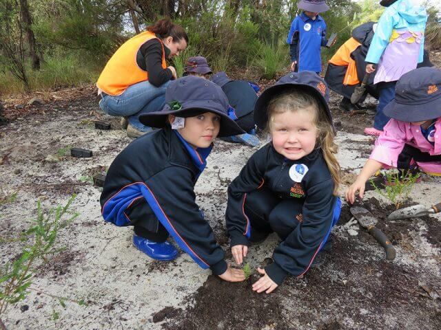 Campbell primary school kindergarten students James Lee and Holly Carter learn about the importance of tree planting.