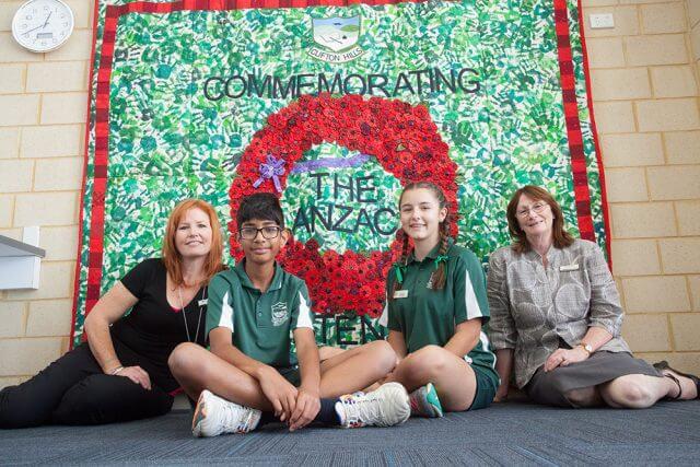 Art teacher Merranie Beal with headboy Akshay Sundru, headgirl Paris Scoby-Smith and principal Patricia Joss in front of the school's mural. Photograph — Matt Devlin.