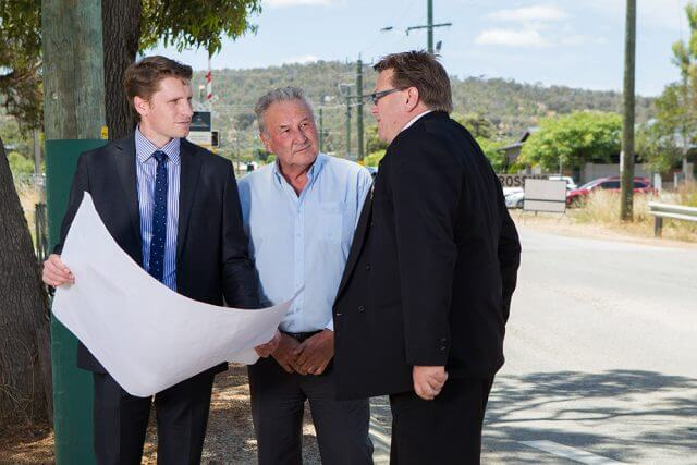Federal Member for Canning Andrew Hastie, Shire of Serpentine Jarrahdale chief executive Richard Gorbunow and shire president John Erren inspect plans for the duplication of Abernethy Road. Photograph — Matt Devlin.