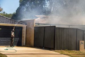 John Geerlings, who was visiting a family member in the street, hoses down a stranger's home to stop the fire from spreading. Photograph - Robyn Molloy.