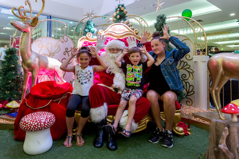 Luana Walters, 9, Chevy Walters, 4 and Jodie-Lee Walters, 12, catching up with Santa at Westfield Carousel last week. Photograph — Kelly Pilgrim-Byrne.